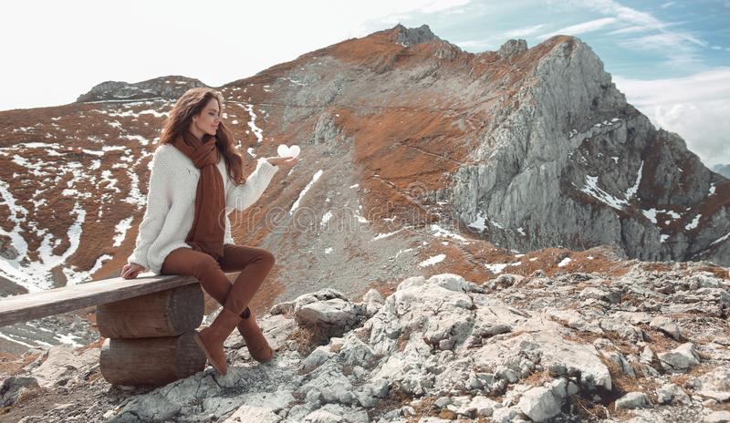 Casual brunette woman sitting on bench holding ice heart enjoying nature above mountains view landscape. Travel Lifestyle. Adventure vacations outdoor. Girl stock image