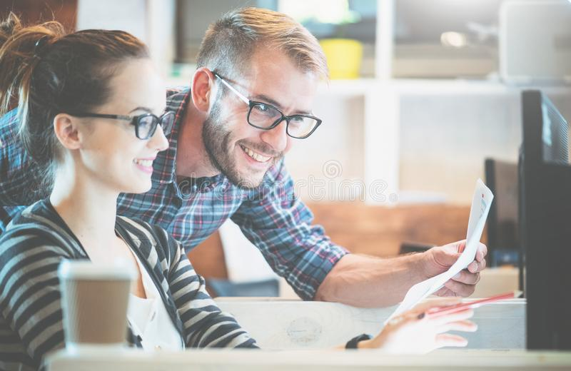 Casual business couple using computer in the office. Two colleagues working together stock photo