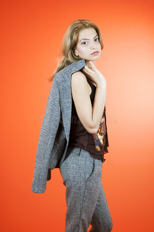 Casual Business Girl. Profile of serious young woman with business jacket flung over her shoulder royalty free stock image