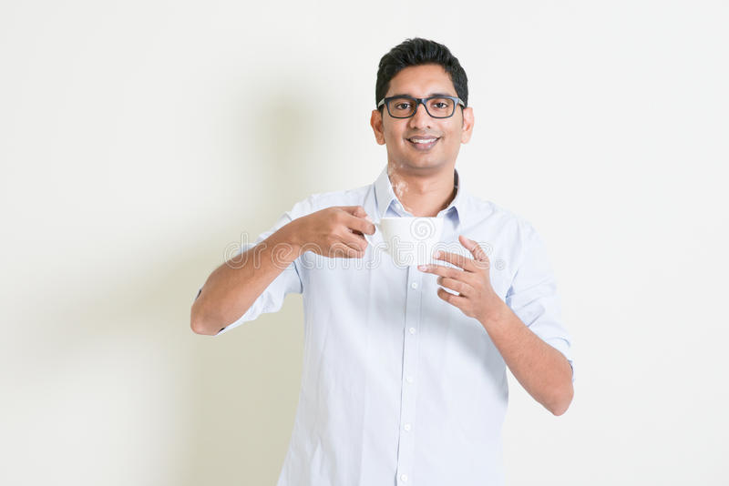Casual business Indian male drinking coffee. Portrait of handsome casual business Indian man relax and drinking a cup hot coffee, standing on plain background stock photos