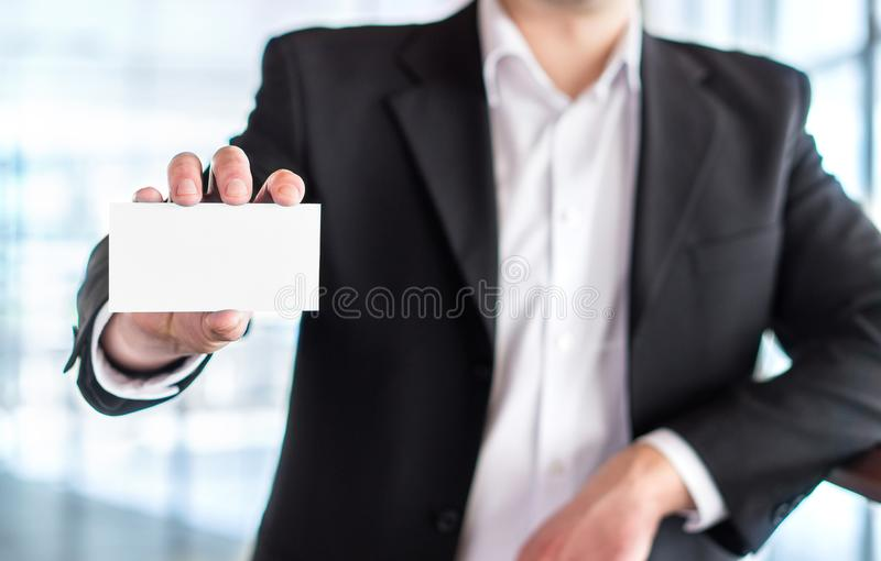 Casual business man holding empty white business card. stock image