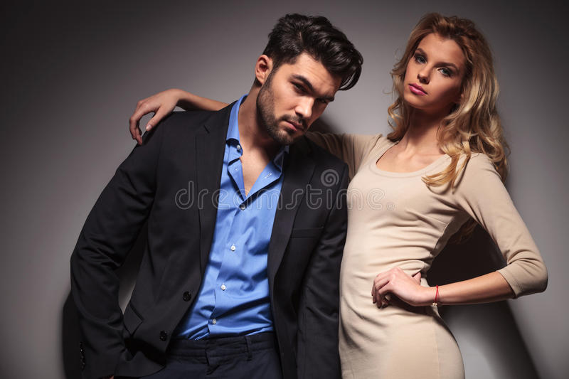 Casual business man leaning on his girlfriend. Casual business men leaning on his girlfriend, both looking at the camera stock photography