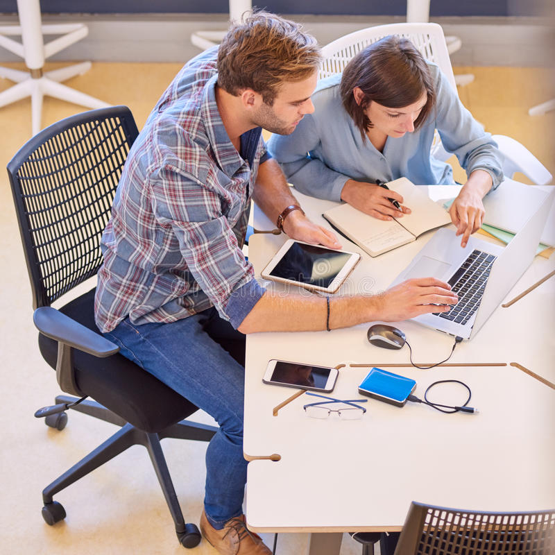 Casual business partners working hard looking at the laptop screen stock images
