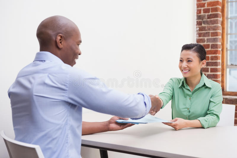 Casual business people shaking hands at desk stock photo
