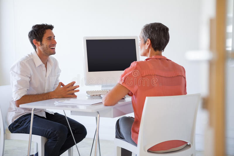 Casual business people talking at desk and smiling stock photos