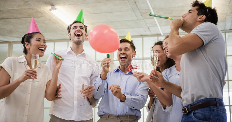 Casual business team celebrating with champagne and party horns stock photography