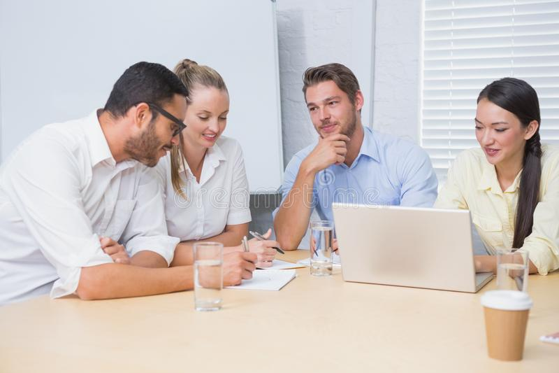 Casual business team having a meeting using laptop royalty free stock photo