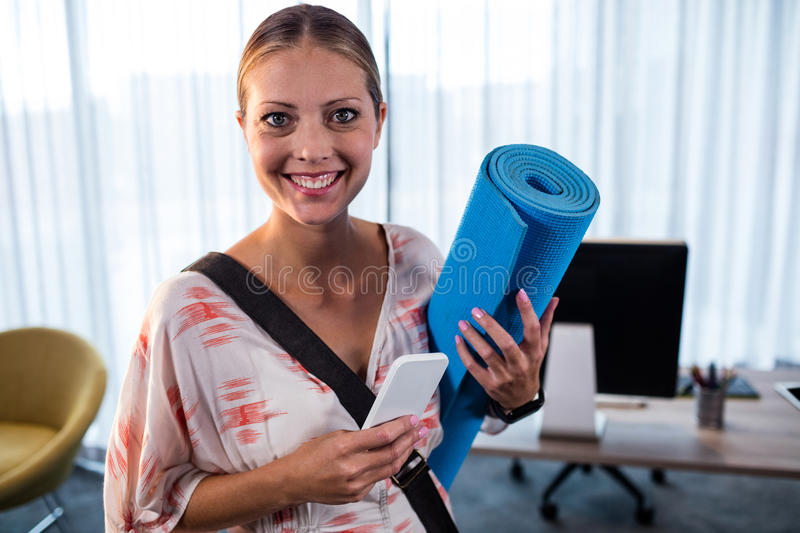 Casual business woman holding yoga mat royalty free stock image