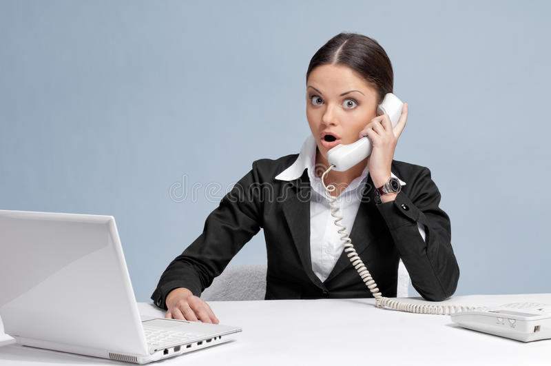 Casual business woman in office talking by phone royalty free stock image
