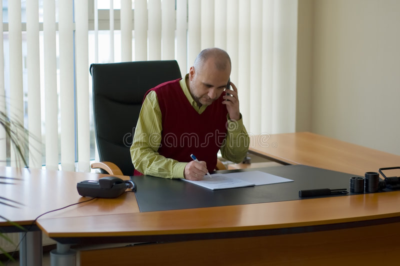 Casual businessman. Studying agreement at his desk by window and speaking on the cellphone stock photos