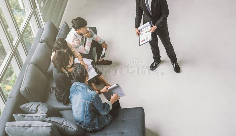 Casual businessman having business meeting with his staff. showing presentation on flip chart. Casual businessman having business meeting with his staff royalty free stock image