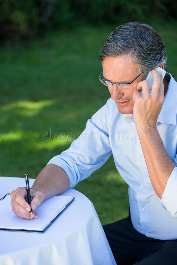 Casual businessman taking notes and having a phone call stock photo