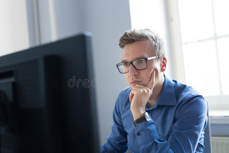 Casual businessman working in office, sitting at desk, typing on keyboard, looking at computer screen. Thoughtful casual businessman wearing eyeglasses, working stock photo