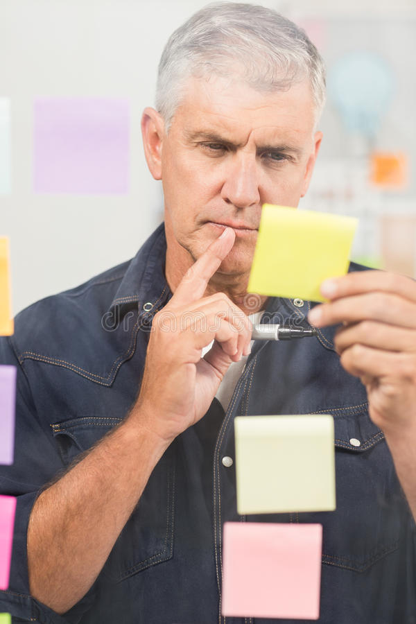 Casual businessman writing on post its stock photos