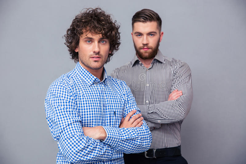 Casual businessmen standing with arms folded. Portrait of a two serious casual businessmen standing with arms folded on gray background stock images