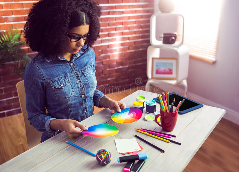 Casual businesswoman holding two color wheel. In her office royalty free stock photo