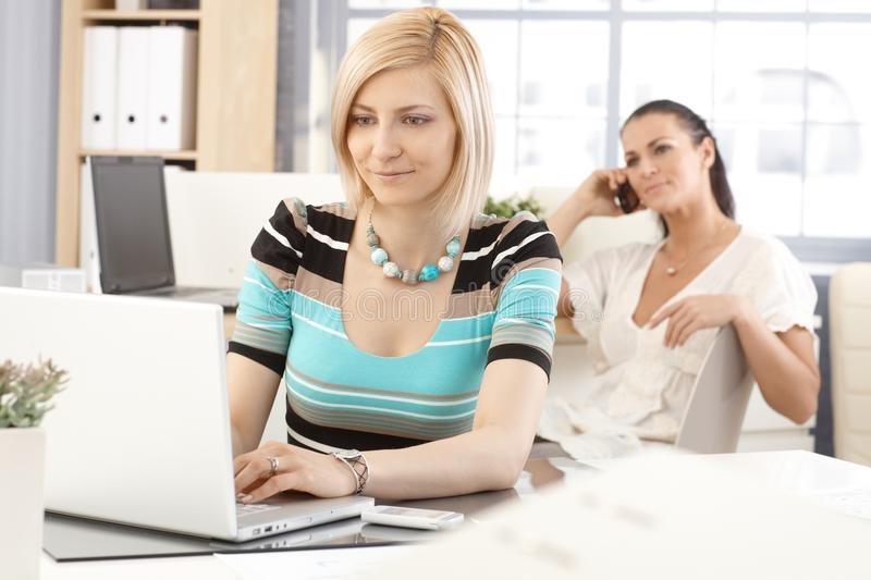 Casual businesswoman working with laptop computer. Happy casual caucasian blonde businesswoman working with laptop computer at office, smiling stock photos