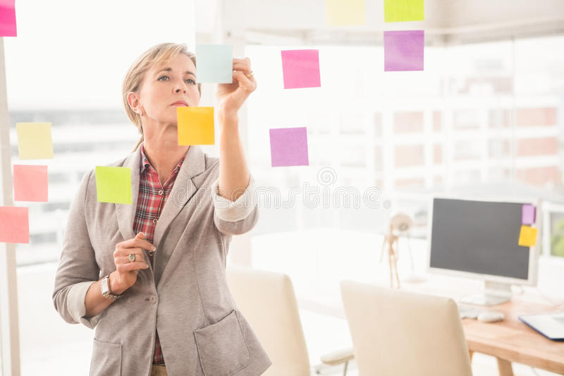 Casual businesswoman writing on sticky notes royalty free stock image
