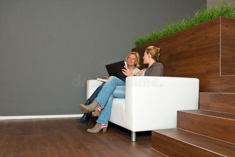 Casual Businesswomen on Couch. Two, casually dressed, business women during an informal presentation, in discussion on a white leather couch in a modern open stock photo