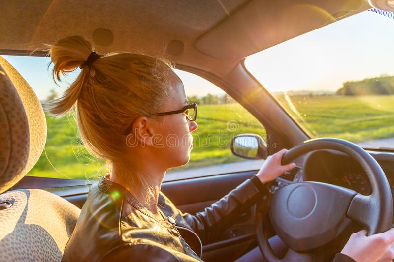 Casual caucasian woman driving passenger car for a journey in countryside. stock image