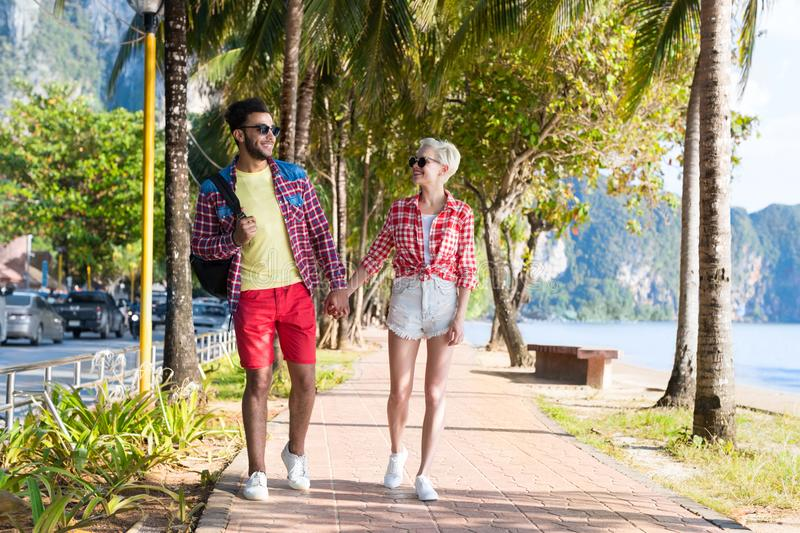 Casual Couple Hold Hands Walking In Tropical Palm Trees Park, Beautiful Young People On Summer Vacation stock image