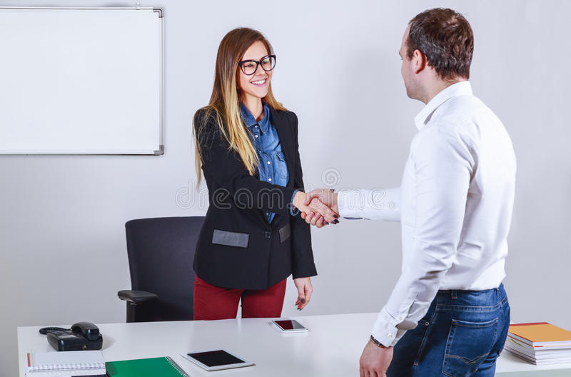 Casual dressed businessmen and businesswoman shaking hands stock photography