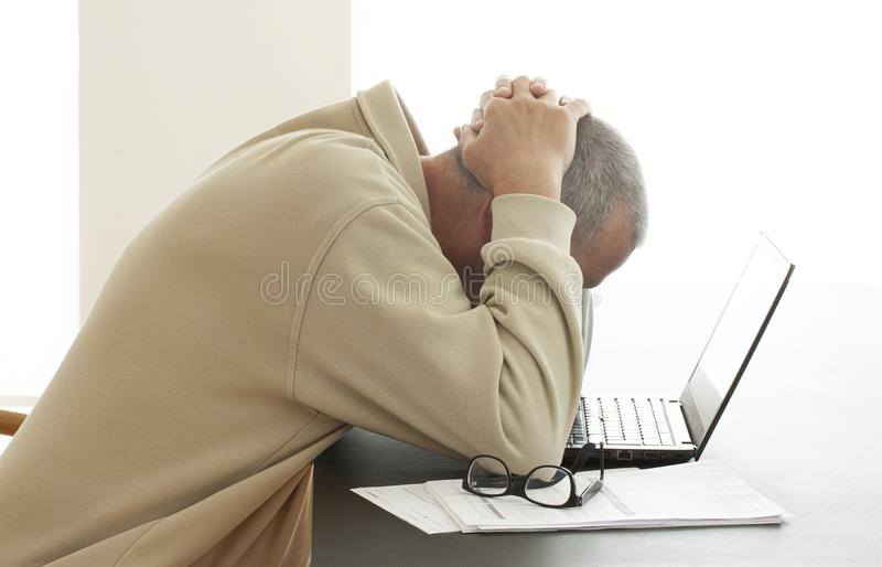 Casual dressed man bends his head over computer in despair while he hides his head in his hands. Pair of glasses lying on a pile o royalty free stock images