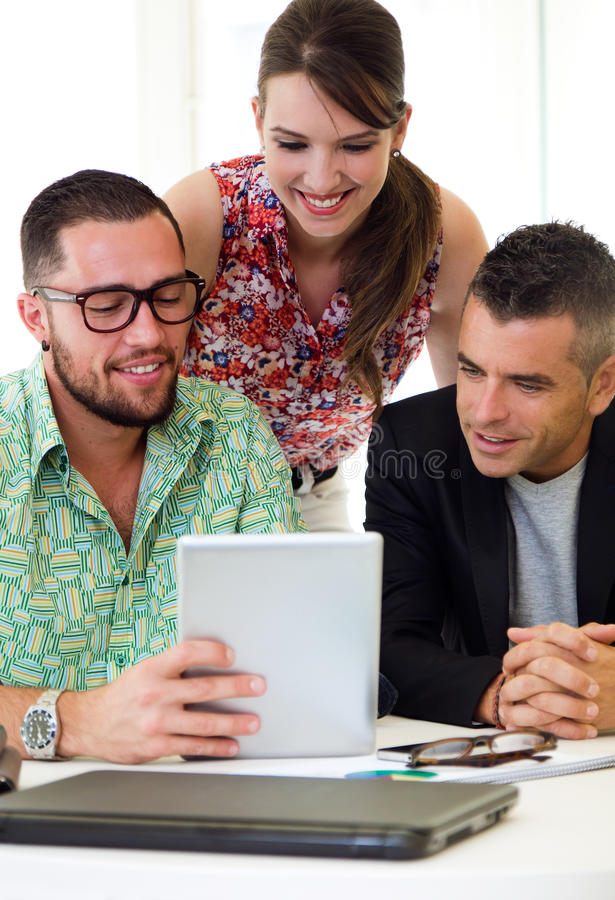 Casual executives working together at a meeting with digital tab. Portrait of casual executives working together at a meeting with digital tablet stock photo