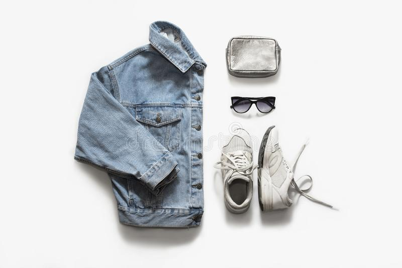 Casual fashion clothes and accessory set on white background. Jean jacket, sneakers, sunglasses, bag. Flat lay, top view royalty free stock photos