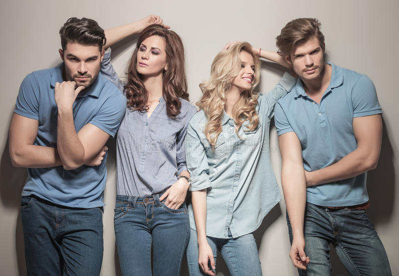 Casual fashion women looking at their men. Two couples of young casual fashion people posing for the camera, women looking at their men royalty free stock photos