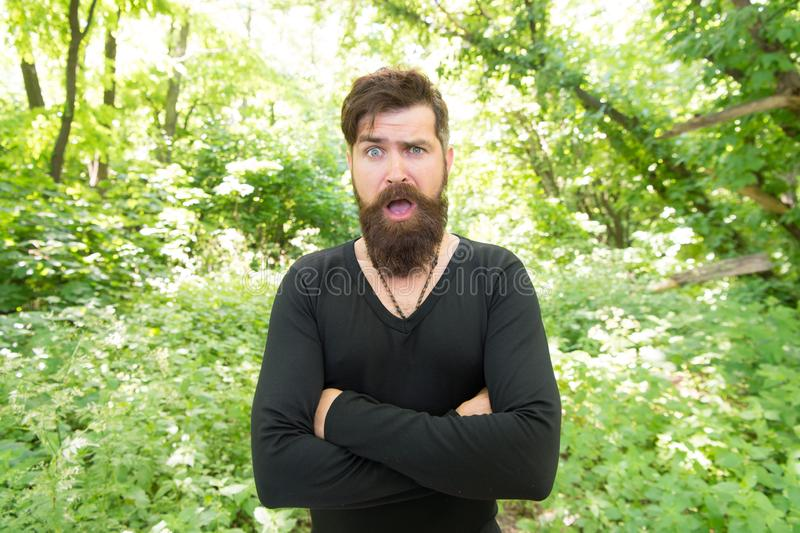 Casual but fashionable. Fashionable look of surprised vogue model on natural landscape. Bearded man in fashionable. Outfit. Fashionable hipster keeping arms stock images