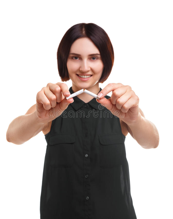A beautiful woman breaking a cigarette isolated on a white background. Youth against smoking. Risk of cancer concept. A casual female is breaking a cigarette royalty free stock photography