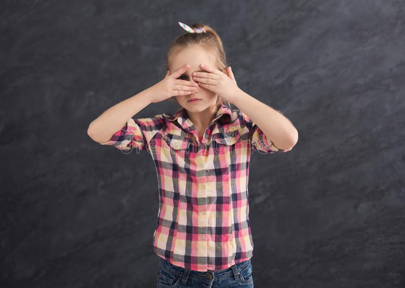 Casual female child covering eyes with hands royalty free stock image