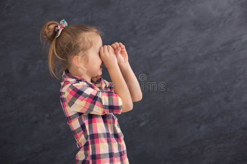 Casual female child holding hands near eyes like telescope stock photography