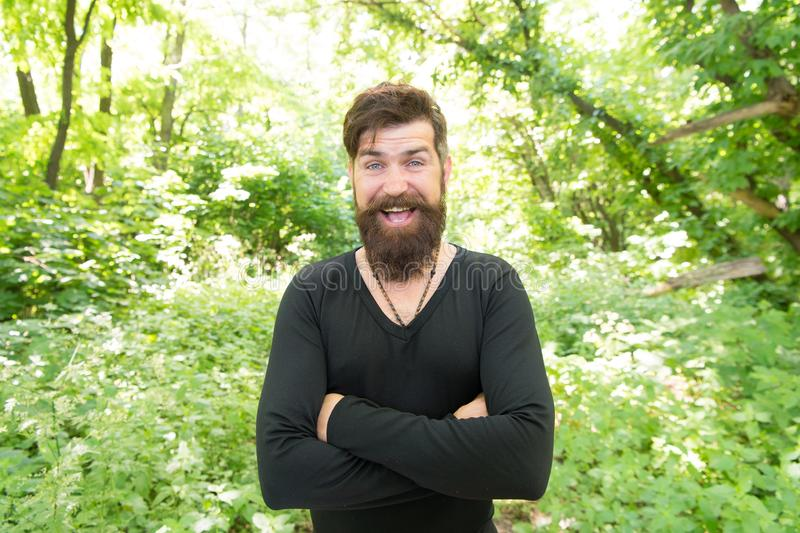 Casual fits him the best. Happy hipster in casual and comfy outfit keeping arms crossed on natural landscape. Bearded. Man smiling in casual style on summer day royalty free stock photography