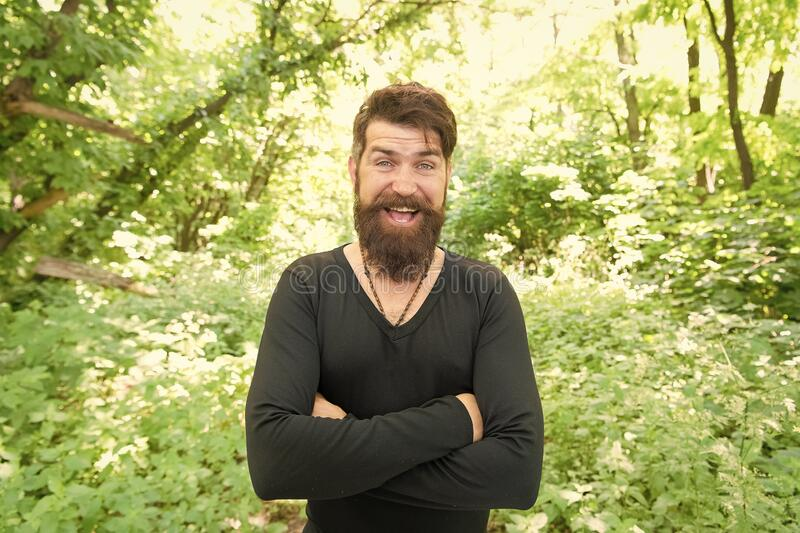 Casual fits him the best. Happy hipster in casual and comfy outfit keeping arms crossed on natural landscape. Bearded royalty free stock image