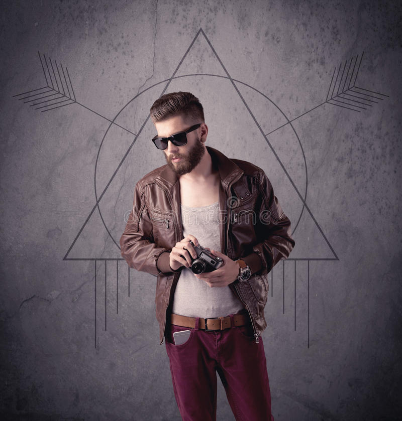 Casual funny male using mobile phone. A young hipster male in modern clothes standing in front of an urban wall with modern sign illustration concept royalty free stock image