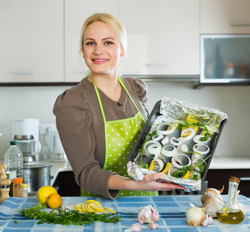 Casual girl with raw fish. On roasting pan at home kitchen stock photos
