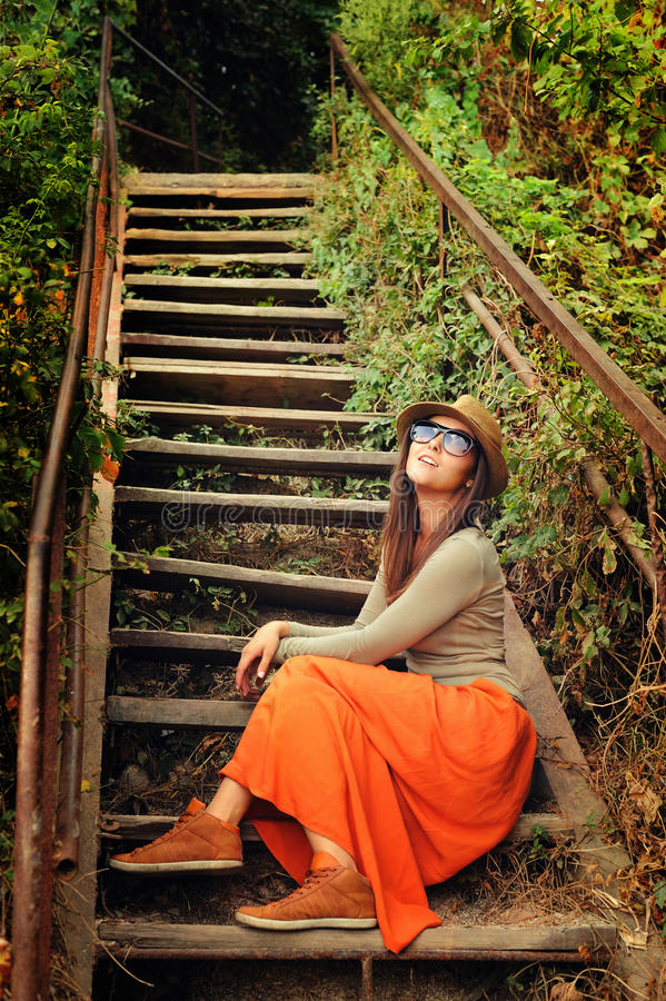 Casual girl wearing long orange skirt sitting on the old wooden stairs. royalty free stock images