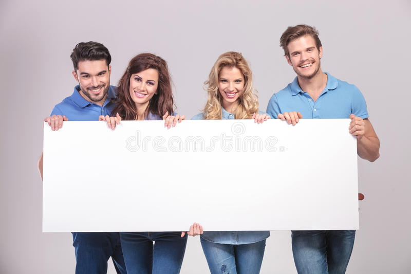 Casual group of young people holding a big blank board stock image