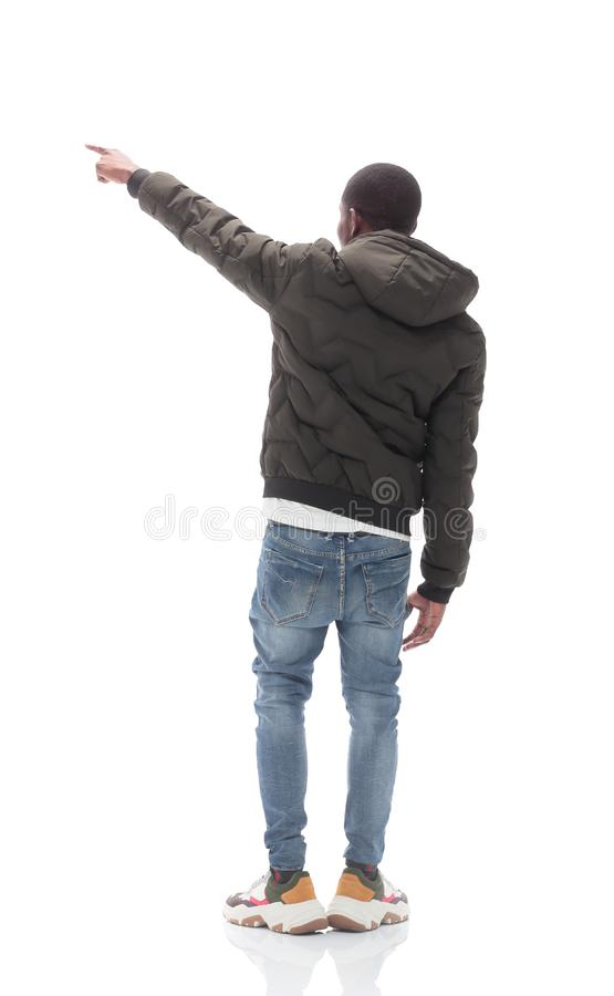 Casual guy in black jacket looking at white wall stock photography