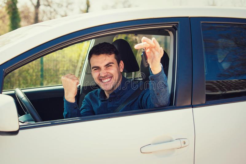 Casual guy driver showing car keys out of the window. Successful young man bought a new car, holding fist up tight celebrating. Triumph. Rental cars or drivers stock image