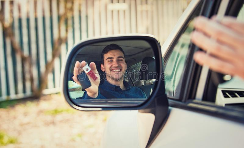 Casual guy driver showing car keys in the side view mirror reflection. Successful young man bought a new car. Rental cars or drivers licence concept, road trip royalty free stock photo