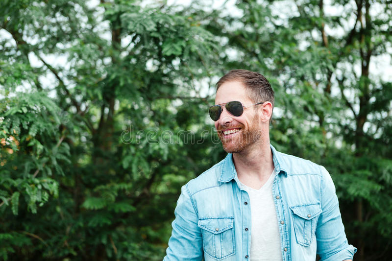 Casual guy relaxed in a park. Casual guy with a sunglasses relaxed in a park stock photos