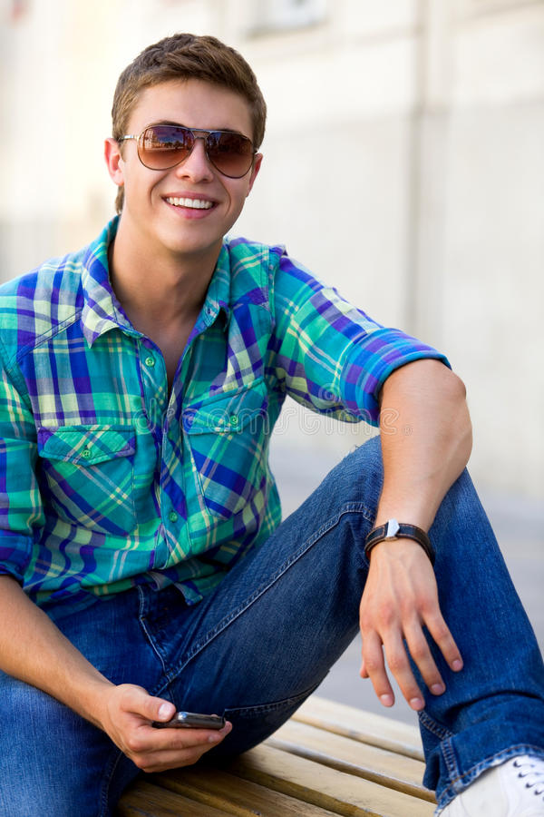 Download Casual Guy Sitting On Bench Stock Image - Image of toothy, teens: 15160695