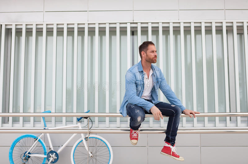 Casual guy with a vintage blue and white bike. Wearing denim shirt stock image