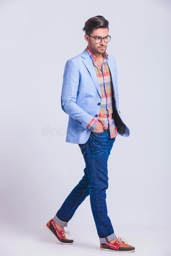 Casual guy walking in studio background with hands in pockets. While posing looking away from the camera stock image