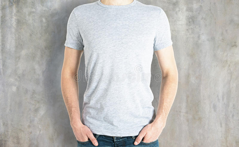 Casual guy in white shirt front. Front view of casual guy in blank white shirt on concrete background. Retail concept. Mock up stock images