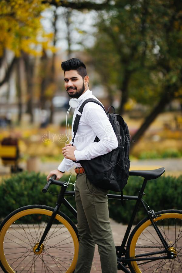 Casual handsome indian businessman pushing bike and carry handsbag going to work by bicycle stock image