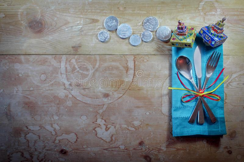 Casual Hanukkah dinner place setting with colorful napkin, dreidels, and gelt on old wood table royalty free stock image